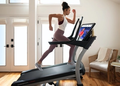 a woman runs on a nordictrack treadmill with iFit